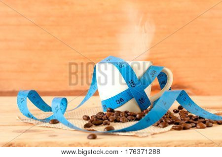 The Hot Coffee In The White Cup With Blue Measuring Tape On Wooden Table And Coffee Seed. Healthy An