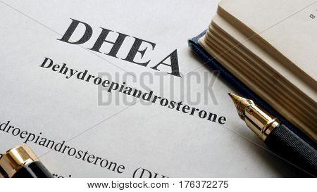 Dehydroepiandrosterone (DHEA) or androstenolone written on a page. Human hormones.