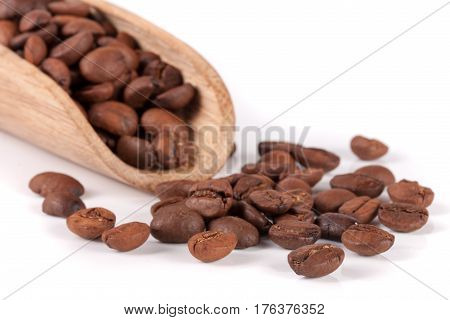 coffee beans in a wooden scoop isolated on white background.