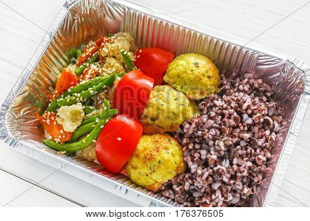 Healthy food restaurant delivery and diet concept. Take away of fitness meal. Weight loss lunch in foil boxes. Falafel with brown rice and vegetables on white wood