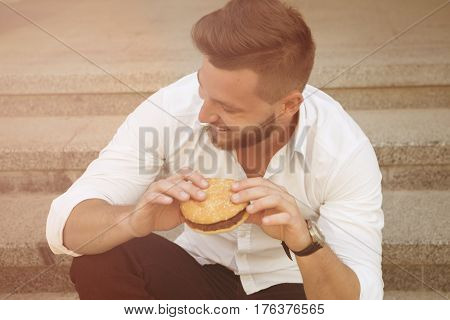 Handsome young businessman wearing white shirt having a snack during his lunch time outdoors. Smiling man eating hamburger. Toned image.
