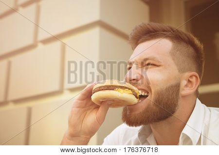 Man eating hot hamburger after stressful work. Close-up of hipster bearded man eating delicious hamburger outdoors. Toned image.