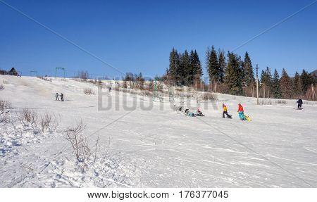 Slavske Ukraine - January 30 2017: Ski resort Slavske in Carpathians. People skiing on mountain slope. Sunny winter day.