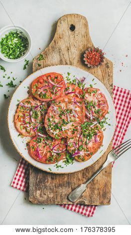 Fresh heirloom tomato, parsley and onion salad in white plate on shabby wooden board over light grey marble background, top view. Clean eating, vegan, vegetarian, healthy, dieting food concept