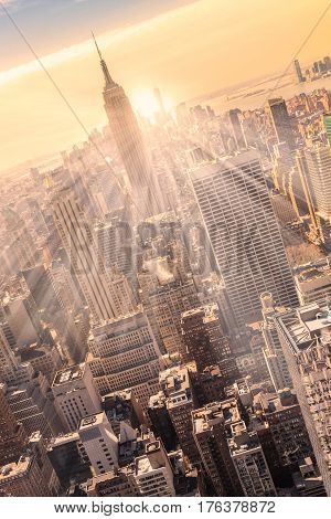 New York City. Manhattan downtown skyline with illuminated Empire State Building and skyscrapers at sunset. Vertical composition. Warm evening colors. Sunbeams and lens flare.