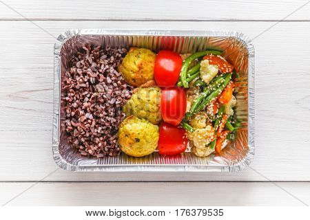 Healthy food restaurant delivery diet concept top view. Take away of fitness meal. Weight loss lunch in foil boxes. Falafel with brown rice and vegetables on white wood