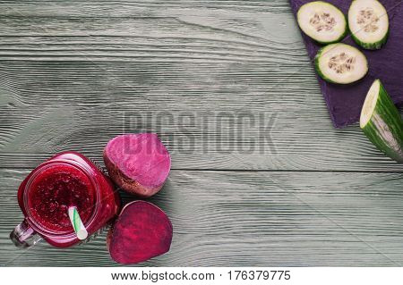 Beetroot smoothie in a mason jar with a straw and ingredients on a wooden background. Fresh beet juice detox top view flat lay. Organic antioxidant smoothies made of beet apple cucumber. Healthy vegan raw food.