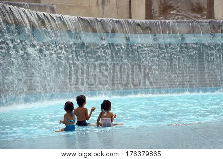 Kuala Lumpur Malaysia - November 5 2014: Children playing in a man-made waterfall in the KLCC Park in Kuala Lumpur Malaysia. This city park was designed by Brazilian architect Roberto Burle Marx.