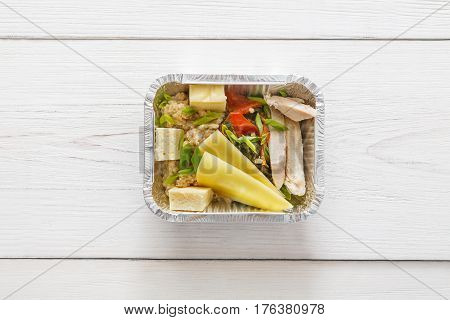 Healthy food take away top view. Weight loss nutrition in foil boxes. Cereal, tofu, meat and vegetables