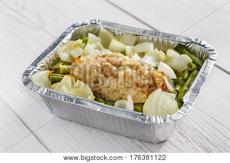 Healthy lunch container. Diet nutrition in foil boxes. Steamed minced meat cutlet with onions and vegetables