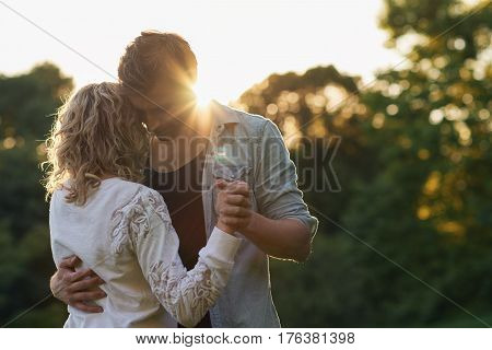 Affectionate young couple dancing hand in hand together while enjoying a romantic moment on sunny summer afternoon in a park