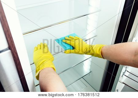 Man's hand in gloves cleaning white fridge with blue rag at kitchen poster