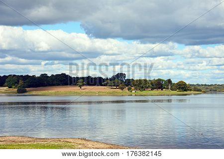 View across Blithfield reservoir towards fields Blithbury Staffordshire England UK.