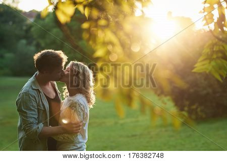 Affectionate young couple kissing each other with their eyes closed while enjoying a romantic sunny summer afternoon together in a park