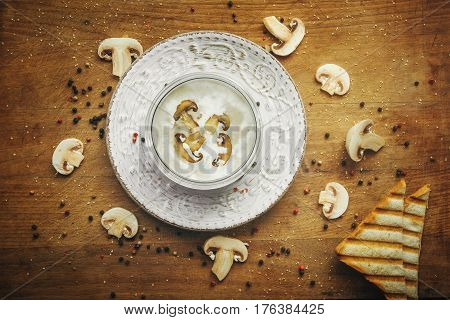 Cream soup with mushrooms champignon in white bowl and circle around plate, bread, vintage style. Top view on desk. Tasty