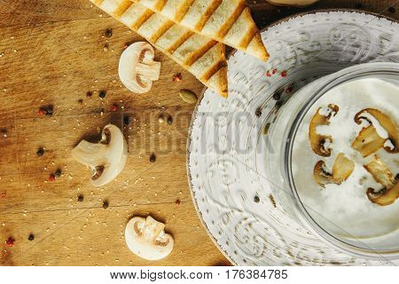 Cream soup with mushrooms champignon in white bowl and circle around part of plate, bread, vintage style. Top view on desk.