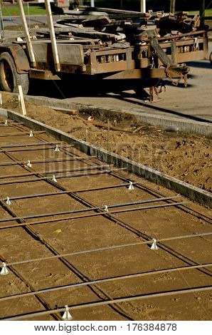 Rebar is in place at a sidewalk construction site with a trailer full of forms in the background