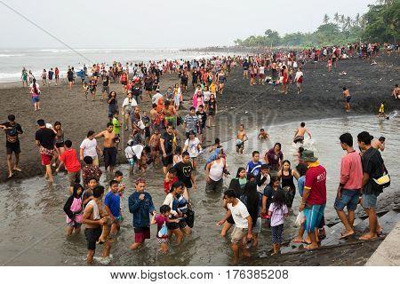 BALI INDONESIA - 22.01.2017: Crowds of people on black sand beach