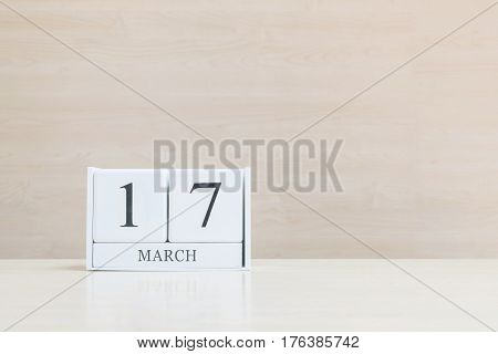 Closeup surface white wooden calendar with black 17 march word on blurred brown wood desk and wood wall textured background with copy space selective focus at the calendar
