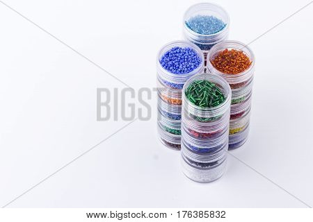 Seed beads storage system. Glass seed beads in tubes for jewelry making and beading process on white background. Hobby handmade fine arts. Selective focus.