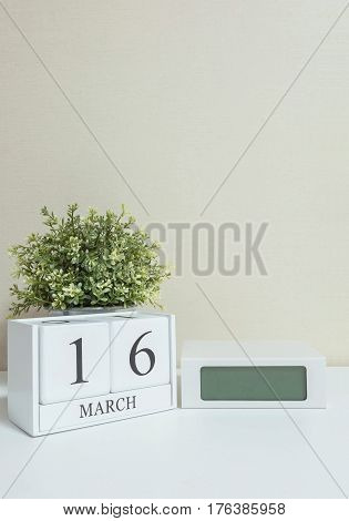 White wooden calendar with black 16 march word with clock and plant on white wood desk and cream wallpaper textured background in selective focus at the calendar