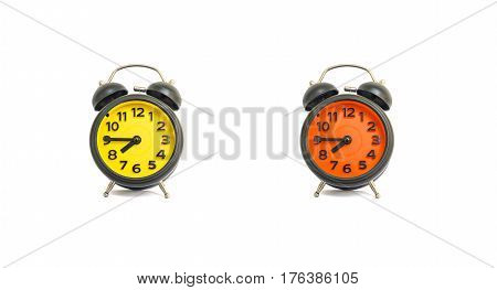 Closeup yellow alarm clock and orange alarm clock for decorate show a quarter to eight a.m. or 7:45 a.m. isolated on white background