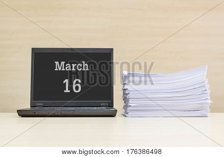 Closeup computer laptop with march 16 word on the center of screen in calendar concept and pile of work paper on wood desk and wood wall in work room textured background with copy space