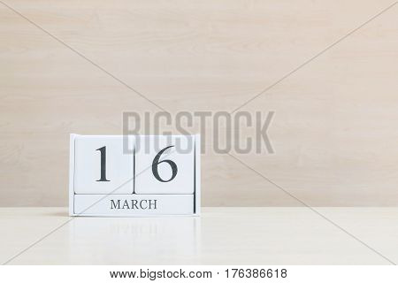 Closeup surface white wooden calendar with black 16 march word on blurred brown wood desk and wood wall textured background with copy space selective focus at the calendar