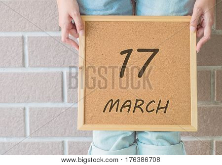 Closeup calendar at the cork board in hand of asian woman in front of her legs with 17 march word on brick wall textured background