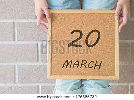 Closeup calendar at the cork board in hand of asian woman in front of her legs with 20 march word on brick wall textured background