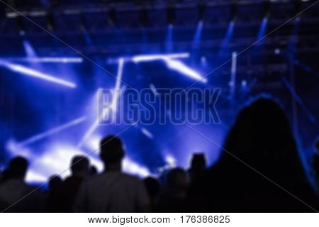 De-focused concert crowd / people silhouettes enjoying music.