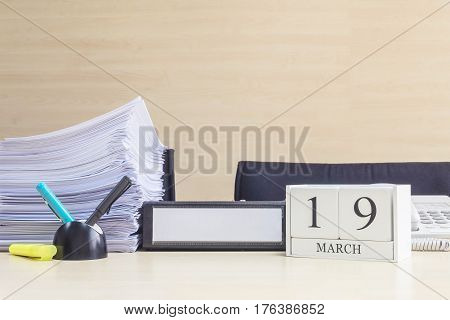 Closeup white wooden calendar with black 19 march word on blurred brown wood desk and wood wall textured background in office room view with copy space selective focus at the calendar