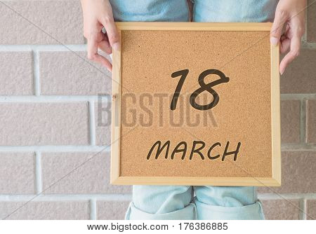 Closeup calendar at the cork board in hand of asian woman in front of her legs with 18 march word on brick wall textured background