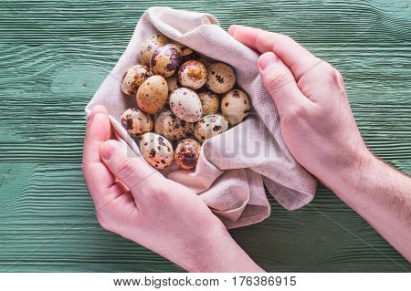 Easter card. Quail eggs on wooden background. Easter eggs. Men's hands hold quail eggs in a linen napkin.