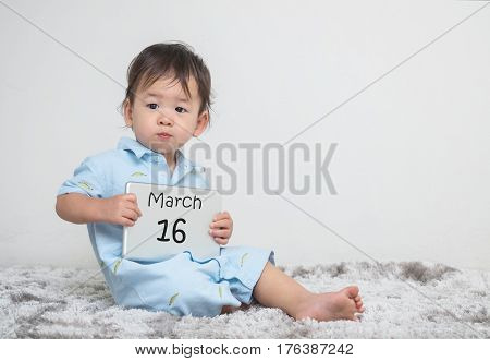 Closeup cute asian kid show calendar on plate in his hand in march 16 word on gray carpet and white cement wall textured background with copy space