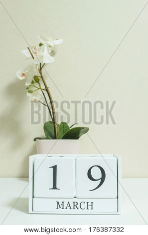 Closeup white wooden calendar with black 19 march word with white orchid flower on white wood desk and cream color wallpaper in room textured background selective focus at the calendar