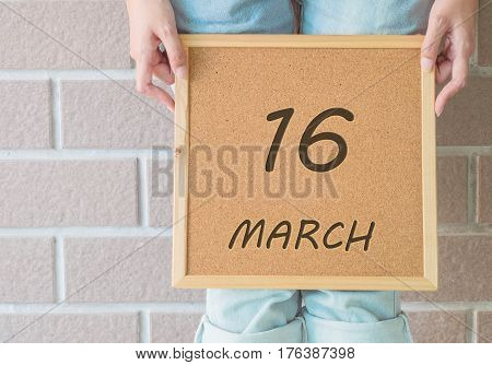 Closeup calendar at the cork board in hand of asian woman in front of her legs with 16 march word on brick wall textured background