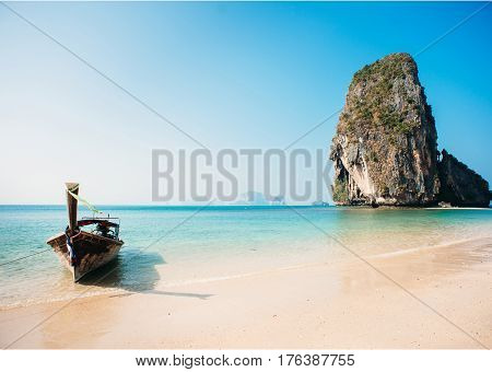 Tropical beach with thai boat and cliff rocks in the sea. Clear water, blue sky. Thailand, Krabi