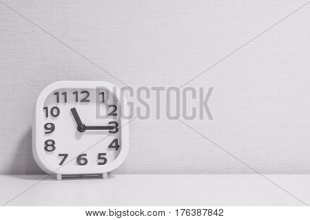 Closeup white clock for decorate show a quarter past eleven or 11:15 a.m. on white wood desk and cream wallpaper textured background in black and white tone with copy space