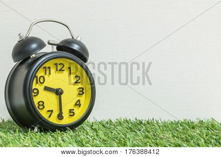 Closeup black and yellow alarm clock for decorate show half past nine o'clock or 9:30 a.m. on green artificial grass floor and cream wallpaper textured background with copy space