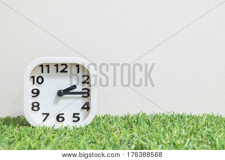 Closeup white clock for decorate show a quarter past two o'clock or 2:15 p.m. on green artificial grass floor and cream wallpaper textured background with copy space
