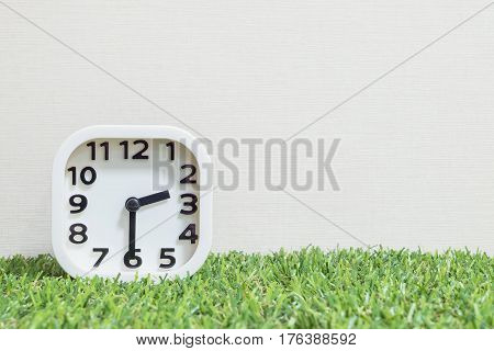 Closeup white clock for decorate show a half past two or 2:30 p.m. on green artificial grass floor and cream wallpaper textured background with copy space