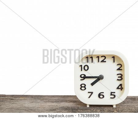 Closeup white clock for decorate show a quarter to eight p.m. or 7:45 a.m. on old brown wood desk isolated on white background with copy space