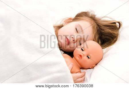 Adorable little girl sleeping in the bed with her doll