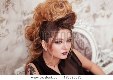 Fashion shiny makeup. Beauty woman with mohawk hairstyle. Blonde sexy model girl with long hair, long eyelashes, perfect skin. Creative unusual mohawk hairstyle. Skincare concept, model head. Rock style. Lady with tattoo