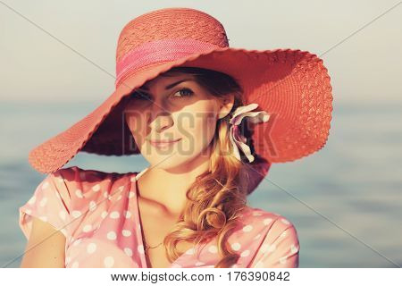 Portrait of a beautiful graceful woman in elegant pink hat with a wide brim. Beauty, fashion concept. Looking in the camera.