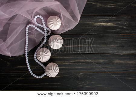 Pink zephyr on dark wooden background with pearl