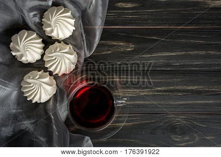 White zephyr with red tea on dark wooden background