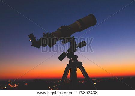 Silhouette of a telescope with de-focused city lights.