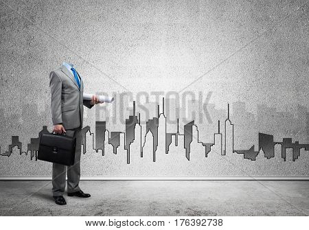 Headless engineer man with papers and case in hand against construction background